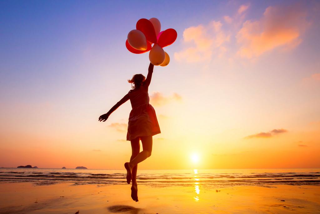 Vrouw op strand met rode ballonnen